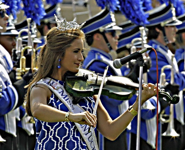 Miss Kentucky Ramsey Carpenter plays the national anthem on her fiddle before the start of the Tennessee-Martin-Kentucky NCAA college football game in Lexington, Ky., Saturday, Aug. 30, 2014. (AP Photo/Garry Jones)